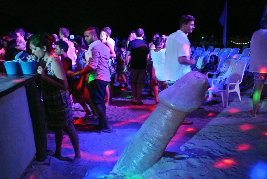 A party---and a large penis coming out of the sand
